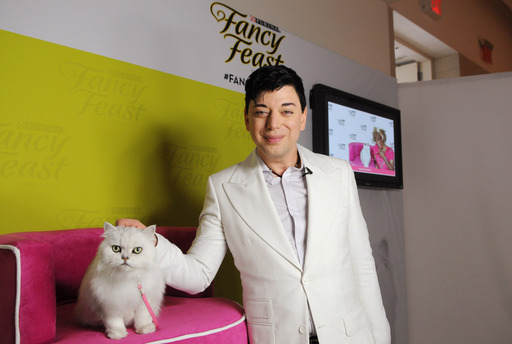 Designer Malan Breton poses with the Fancy Feast cat at his STYLE360 show during New York Fashion Week. Breton's collection featured four looks inspired by the iconic Fancy Feast cat.
