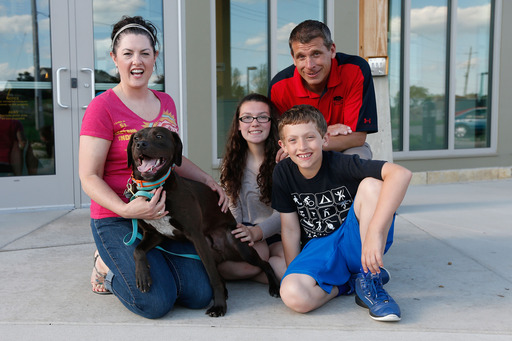 Adopted dog, Kane, poses with his new family, the Millers. Kane took the ride of his life aboard the PetSmart Charities® Rescue Waggin'® vehicle from Tenn. to Wis. (Scott Boehm/AP Images).