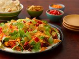 Layers of sour cream, seasoned beef, cheesy rice and fresh toppings make for one delicious taco salad.