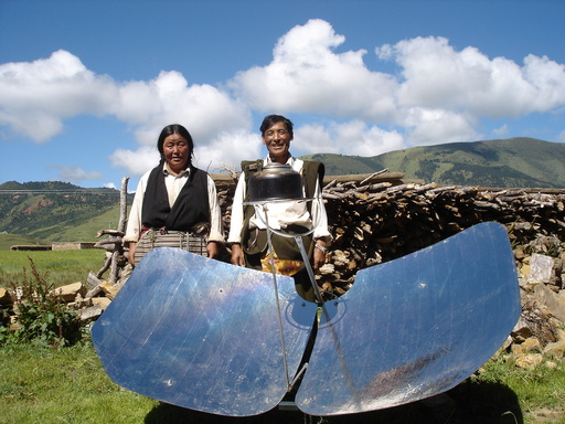 A husband and wife with their solar cookstove in China. Photo credit: Global Alliance for Clean Cookstoves