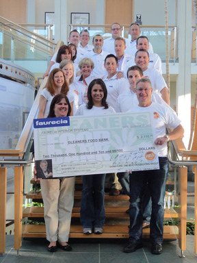 Employees from Faurecia's Auburn Hills, Mich.-based tech center present a check for $2,110 to the Gleaners Food Bank based in Detroit. The money will be used to buy 52,750 pounds of apples!