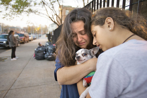 Retired New York City police officer Desiree Marino and daughter Angelika hug their Chihuahua, Tiger, outside a homeless shelter. PetSmart Charities provided housing for Tiger following the storm.