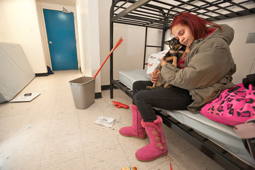 Shanna Nevarez of Rockaway Queens, New York, clings to her miniature pinscher, Pedro, at a homeless shelter. PetSmart Charities cared for Pedro while Shanna got back on her feet.