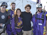 "Professional skater Paul Rodriguez poses with MaryJo Villar, winner of the Takis Airdrop ""Face the Intensity"" photo contest, and members of the World Wingsuit League  in Pomona CA."