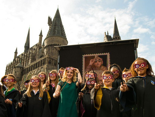 Evanna Lynch, Luna Lovegood in the Harry Potter films, in her signature Spectrespecs, unveils the USPS Harry Potter Limited-Edition Forever stamp collection at The Wizarding World of Harry Potter at Universal Orlando Resort.