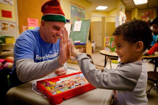 "Team Hasbro employee Justin Kreter celebrates a successful game of Operation with a youth student during a ""Game Day"" service project on Hasbro's Global Day of Joy."