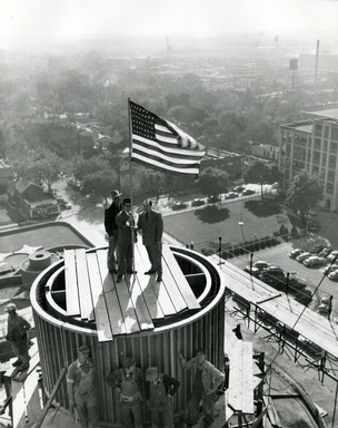 H.F. Johnson and Frank Lloyd Wright flying an American flag from the Tower's rooftop during construction in 1949