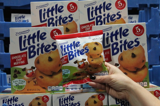 An Entenmann's Little Bites pouch is shown in front of stacked Little Bites boxes at the manufacturing facility in Albany, NY