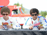 "Fierce racing rivals, business partners and true friends, Tom ""The Mongoose"" McEwen (Richard Blake) and Don ""The Snake'"" Prudhomme  (Jesse Williams) sign Hot Wheels cars in a scene from ""Snake and Mongoo$e."""
