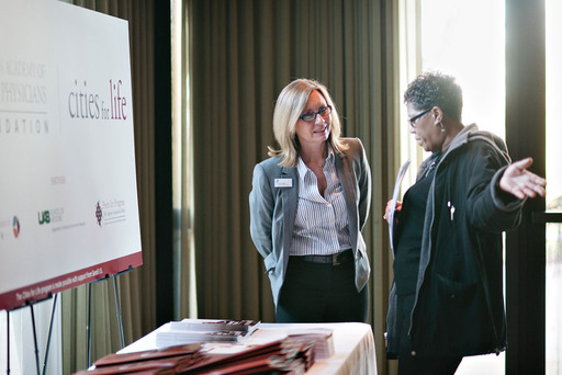 A member of the Cities for Life Steering Committee briefs an attendee on the Community Action Team, which helped provide information on community resources available to people living with diabetes.