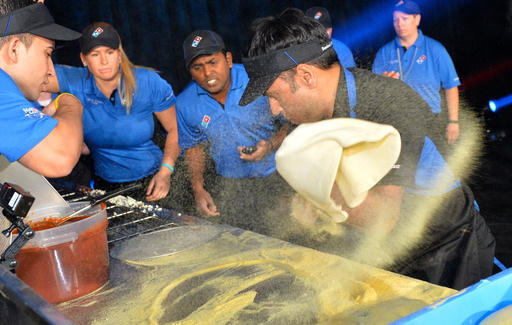 Pali Grewal stretches the dough as he competes in Domino's 2014 World's Fastest Pizza Maker Competition.