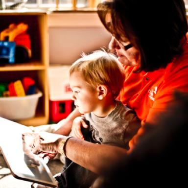Teacher and young child read together