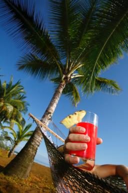 Enjoying a tropical beverage on a hammock in Hawaii