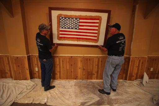 Volunteers rehang the centerpiece American flag