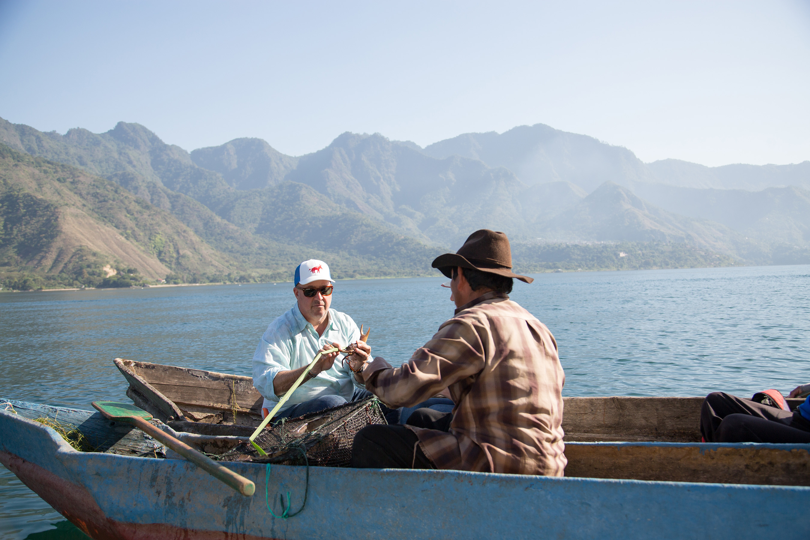 Host Andrew Zimmern learns how to wrap crabs in tule reeds for safe keeping from local fisherman Manuel Toc on Lake Atitlan.