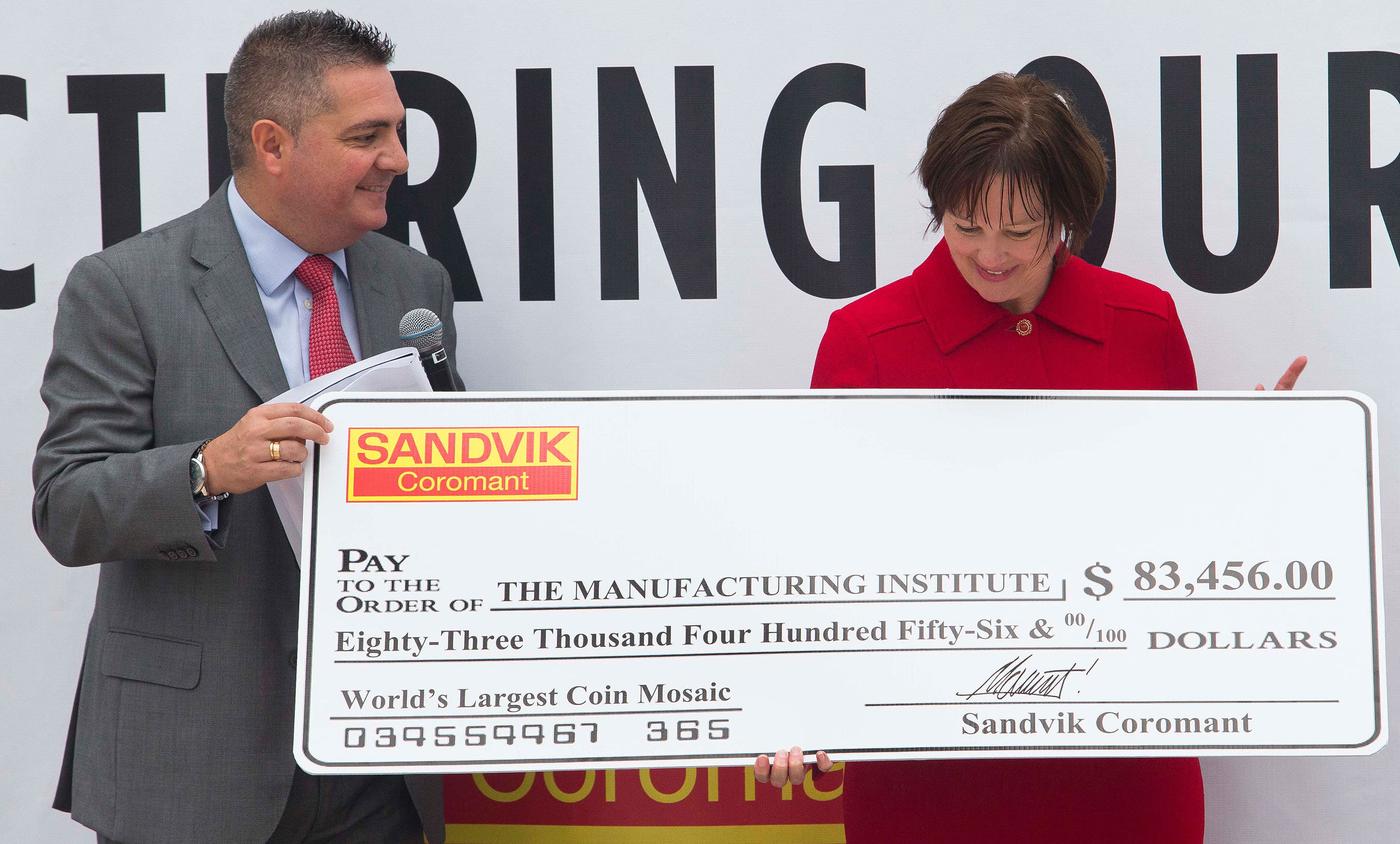 "Eduardo Martin, President, Market Area Americas, Sandvik Coromant, left, presents Jennifer McNelly, President, The Manufacturing Institute, a check for $83,456 to further the advancement for STEM (Science, Technology, Engineering, and Mathematics) education for future generations as part of Sandvik Coromant breaking the Guinness World Record for the ""World's Largest Coin Mosaic"" on Wednesday, Sept. 10, 2014 in Chicago. Photo: Sandvik Coromant"