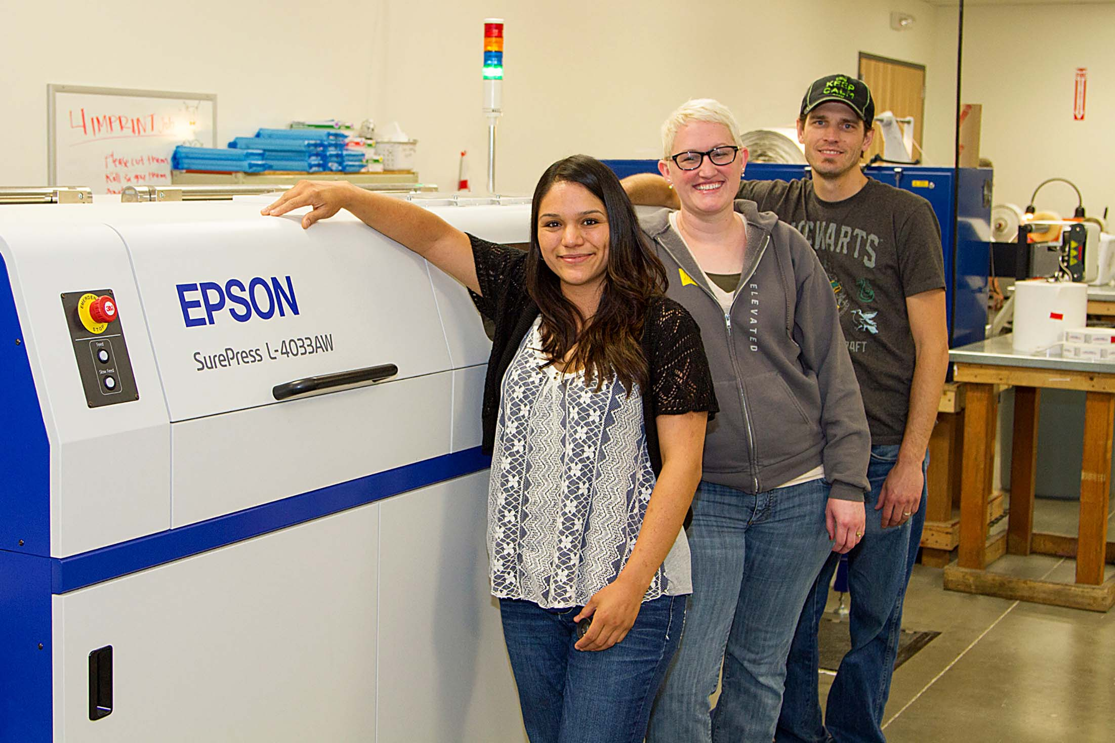 From left to right: Violeta Avalos, Jennifer Imes, and Nathan Champlin from SnugZ USA with the SurePress L-4033AW.