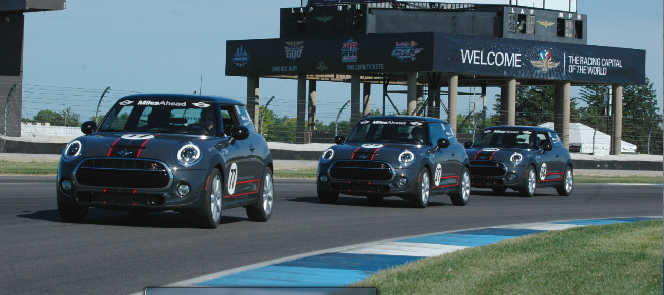 A fleet of MINI Hardtops take to the track at the Indianapolis Motor Speedway as part of a safety program by MINI USA and Miles Ahead Driving School aimed at educating teens on non-distracted driving.
