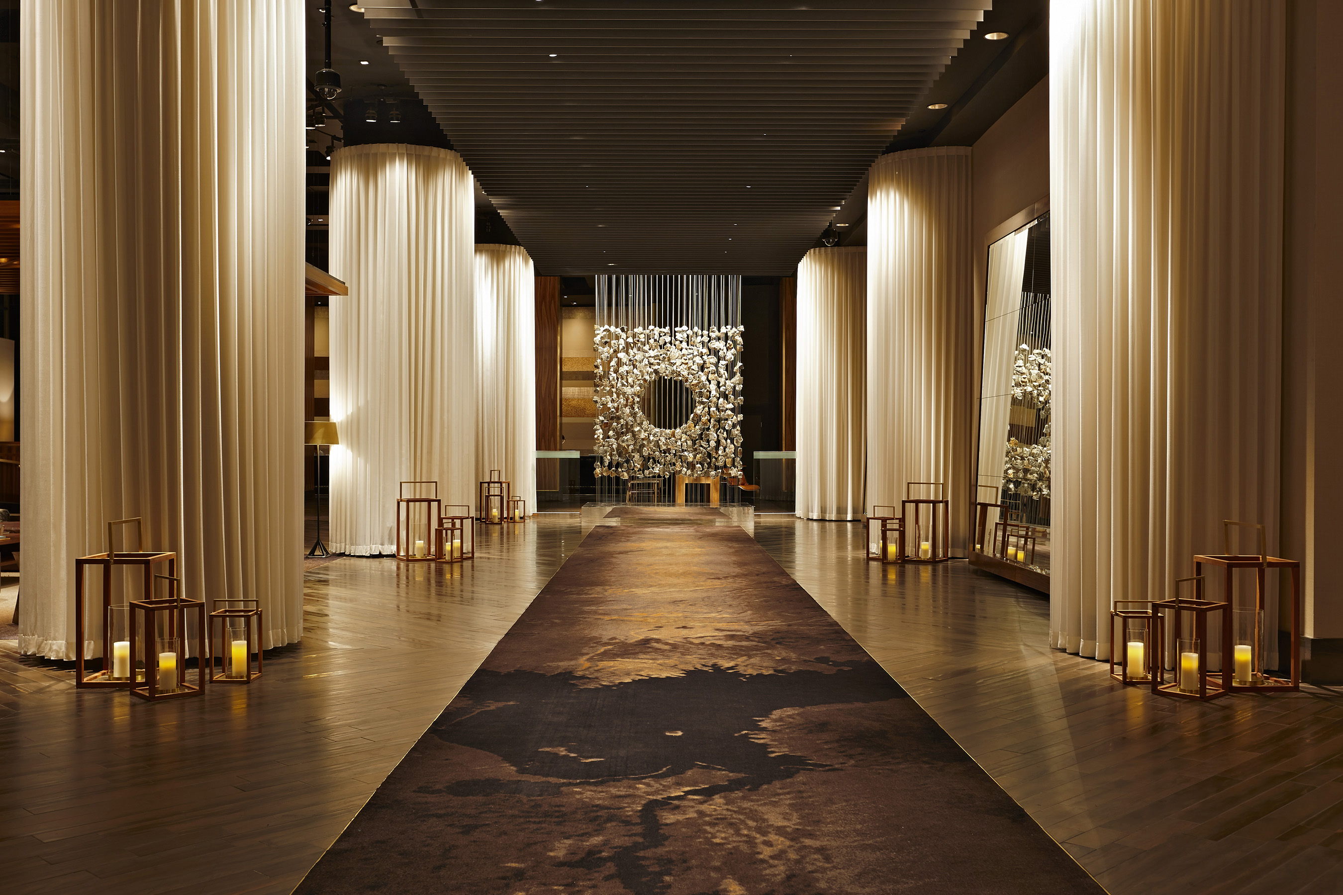 In Delano Las Vegas' lobby, striking columns wrapped in signature white sheers frame a suspended art installation comprised of hundreds of small rocks by renowned Korean artist Jaehyo Lee.