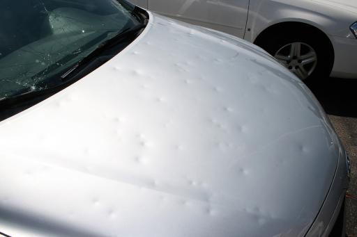 Hail damage to windshield and hood of car