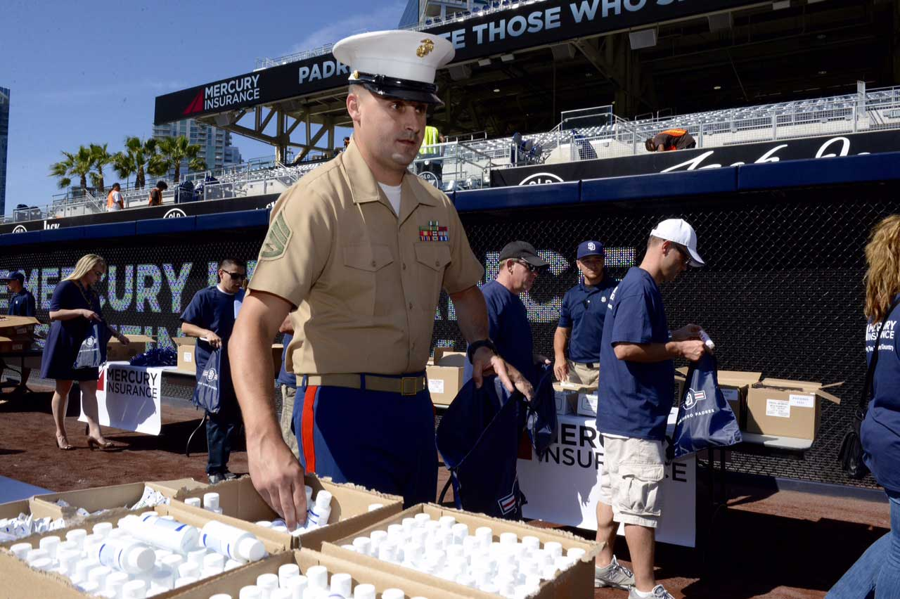 Mercury employees and agents fill packages for Marines and Sailors overseas. Each package includes a Padres backpack, hat, notecards and baseball, along with a bag of Cracker Jack and toiletries.