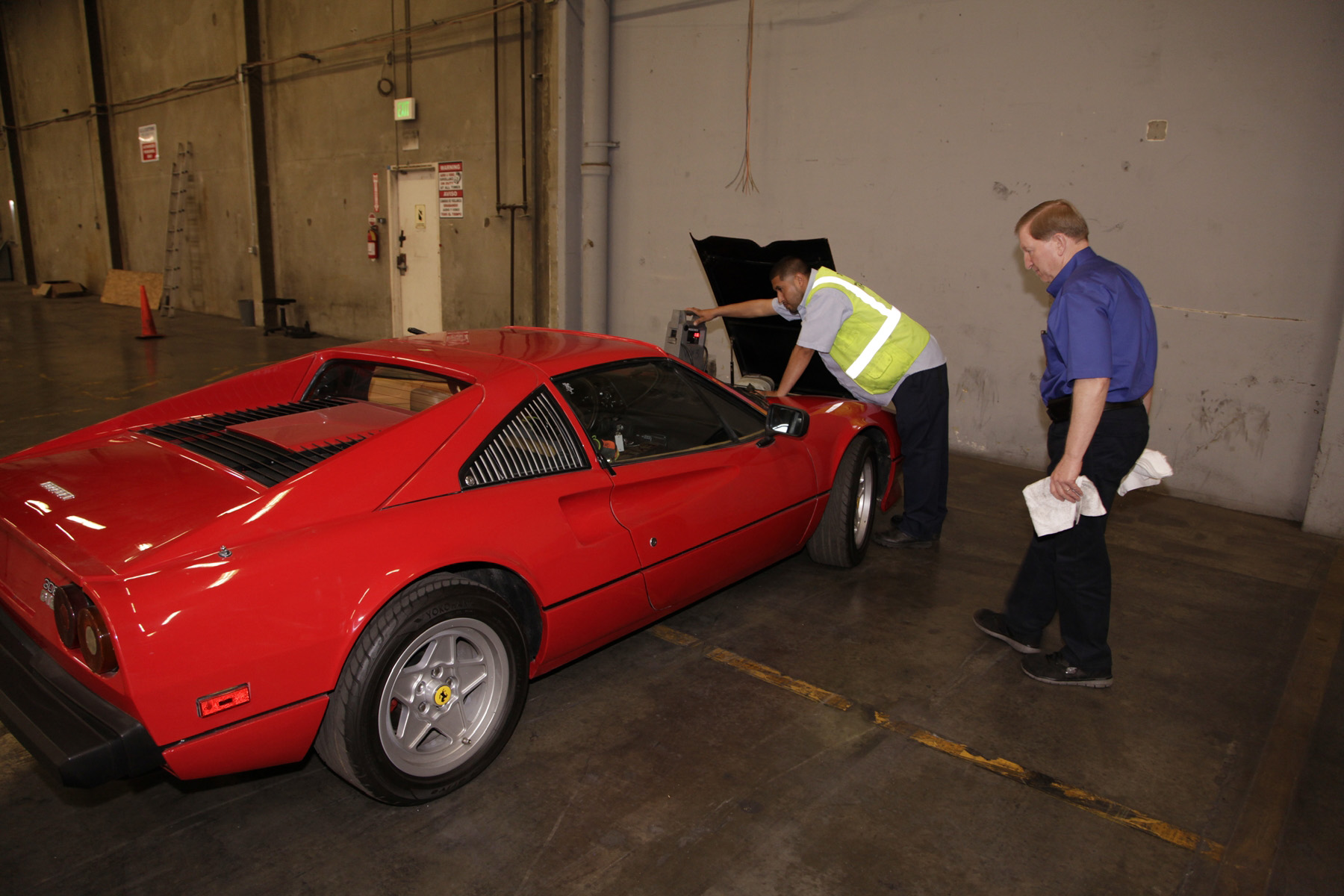 NICB Special Agent Lou Koven (right) looks over the stolen 1981 Ferrari.