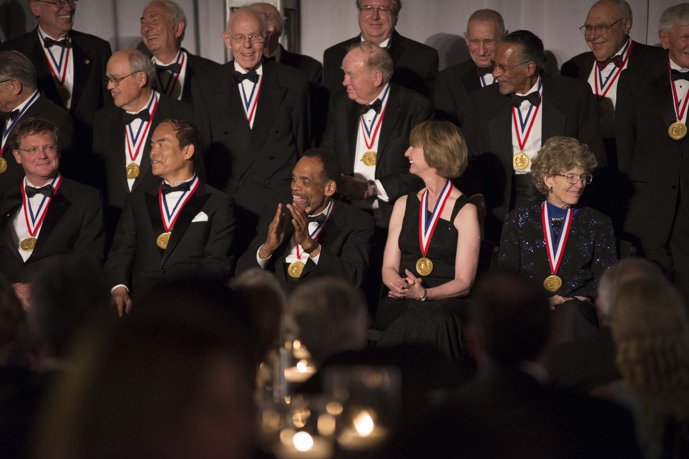 """2015 National Inventors Hall of Fame Inductees chat during """"class"""" photo shoot."""