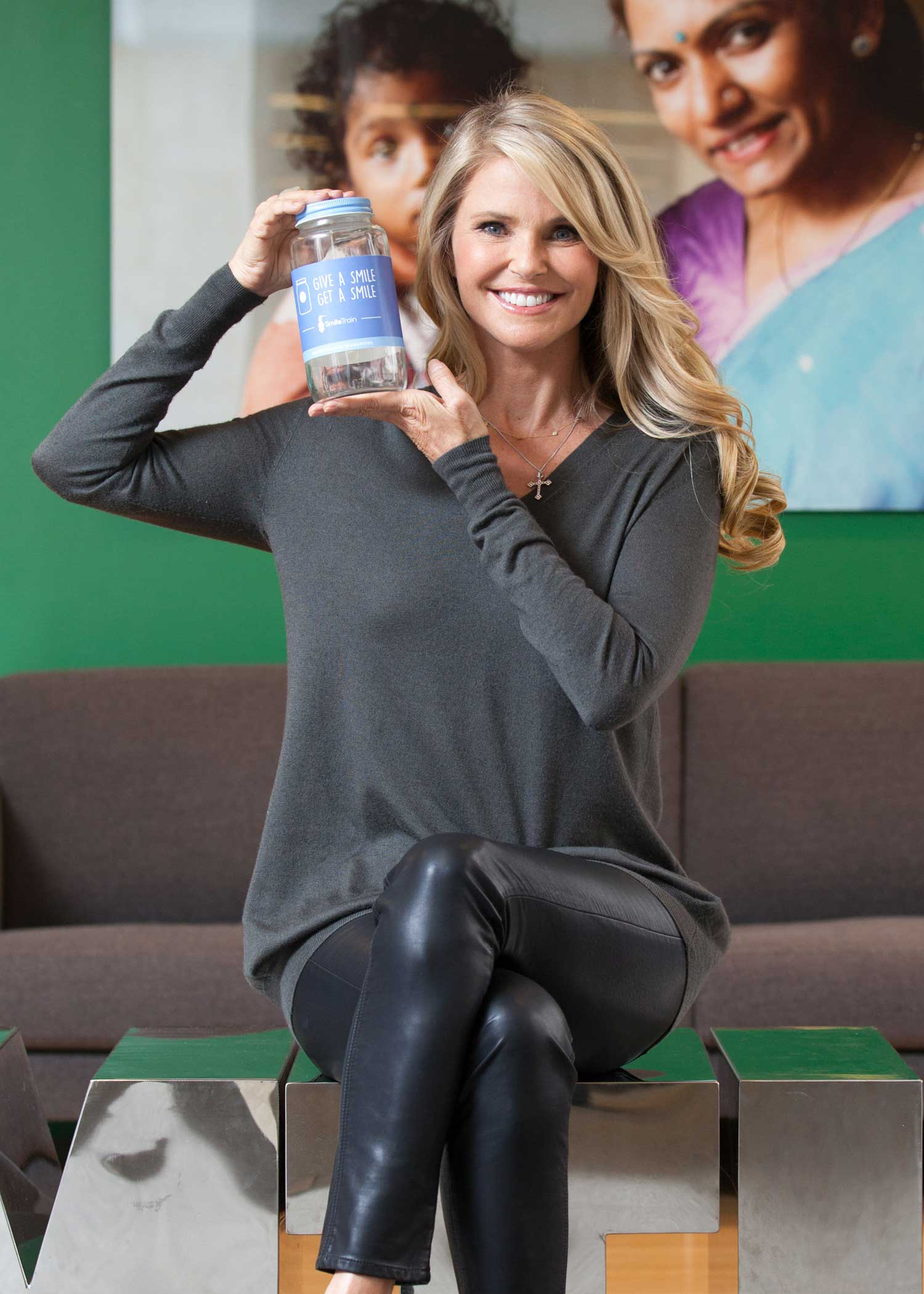 "Christie Brinkley holds up a real-life ""Smile Jar"" to activate support for Smile Train's ""Give a Smile, Get a Smile"" campaign."