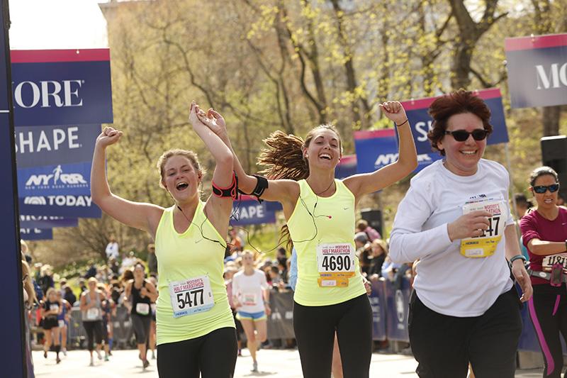 Friends celebrate crossing the finish line at the 2015 MORE/SHAPE Women's Half-Marathon