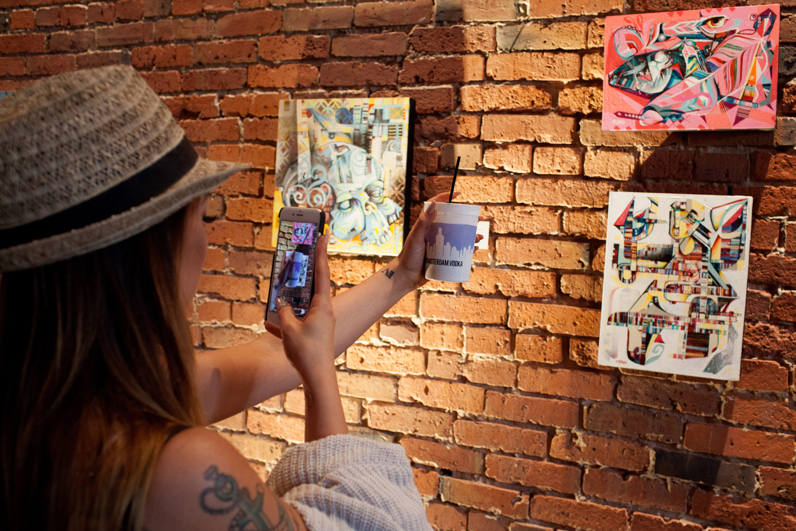 """A guest snaps photos while checking out John Osgood's Seattle-inspired street art at """"It's Your Town,"""" presented by New Amsterdam Vodka at Axis Pioneer Square on Wednesday, April 6, 2016 in Seattle."""
