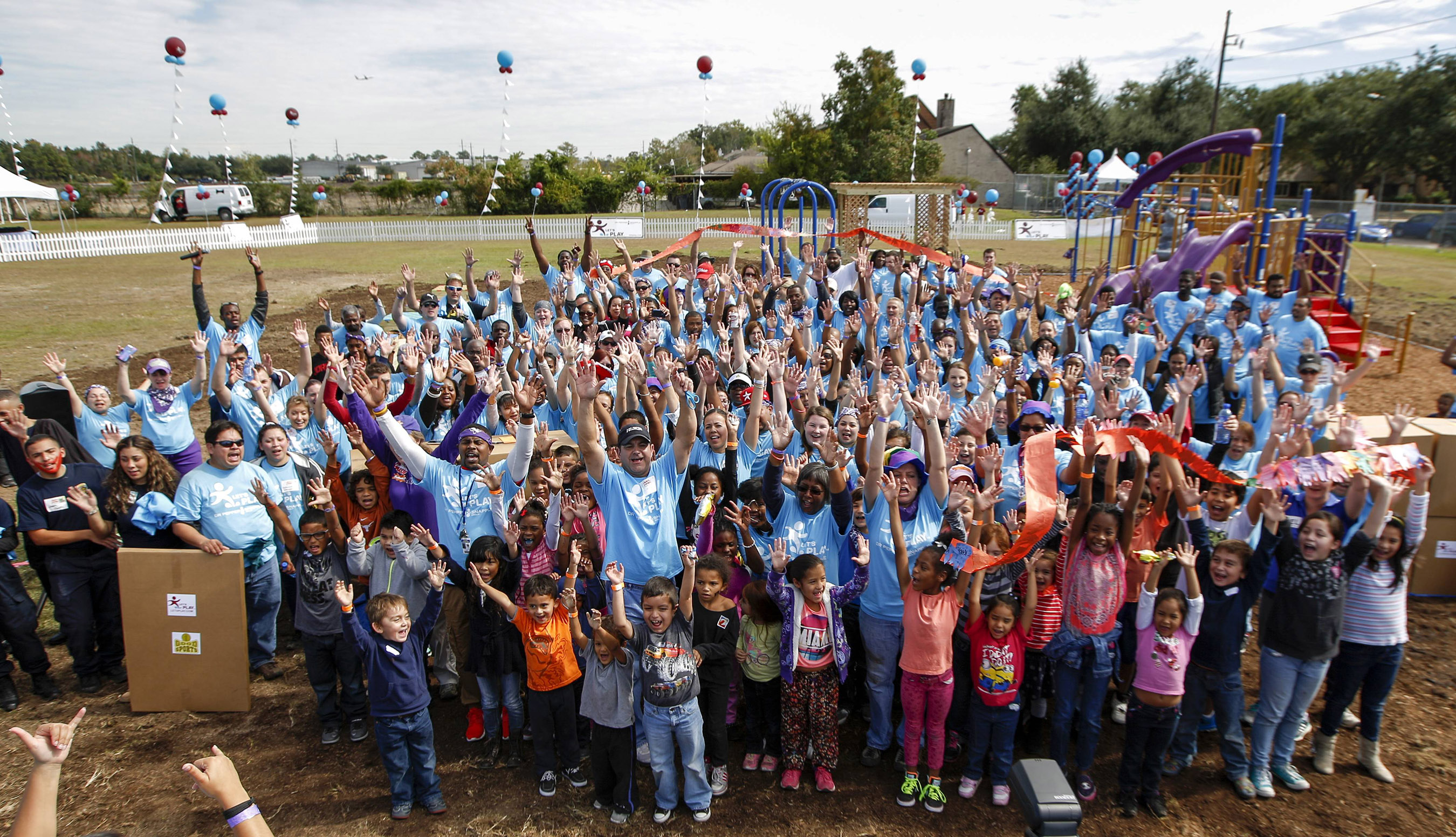 Let's Play Houston volunteers celebrate completion of playground construction with local children