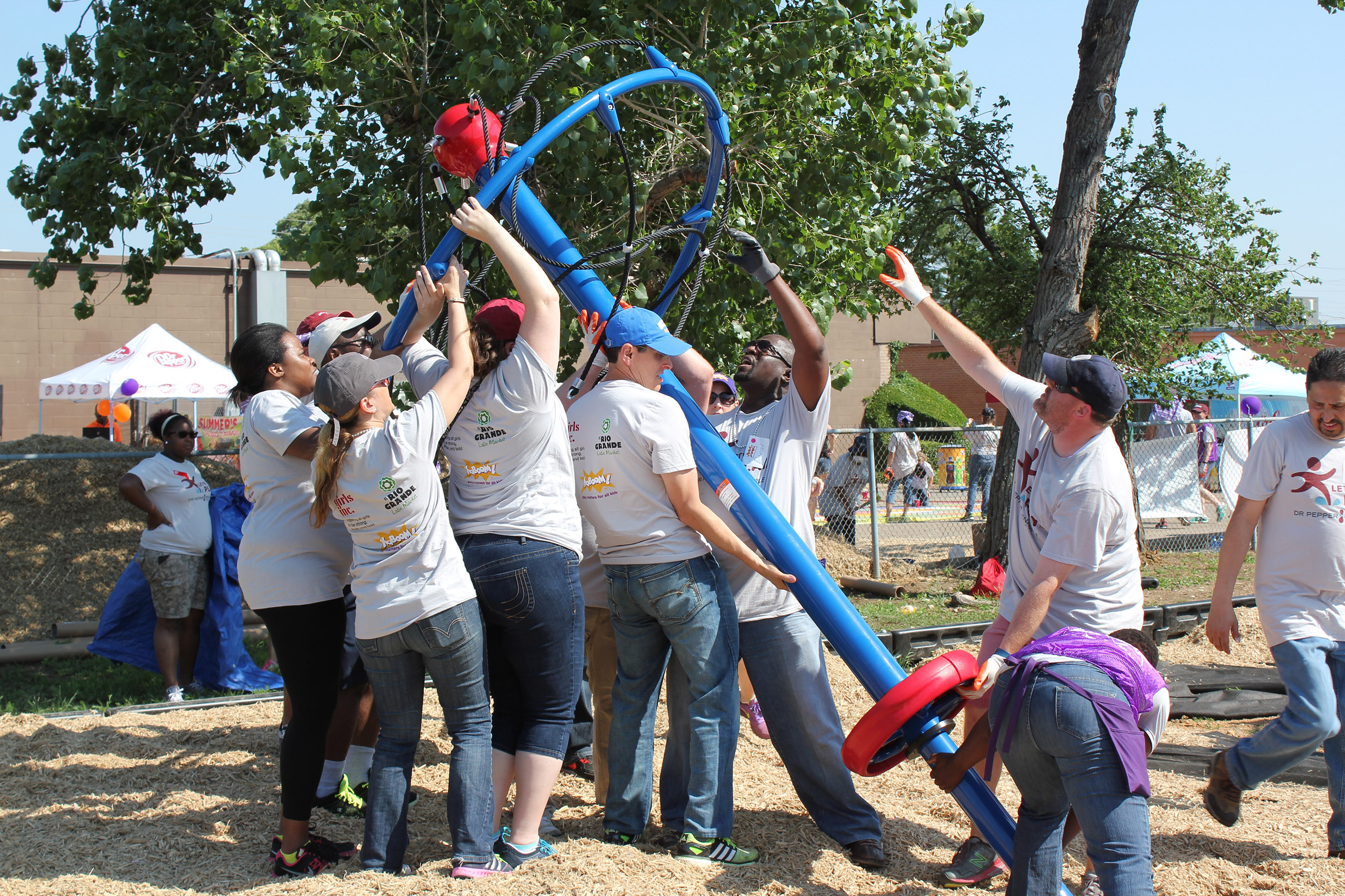 Volunteers hoist play structure at Let's Play Dallas playground build