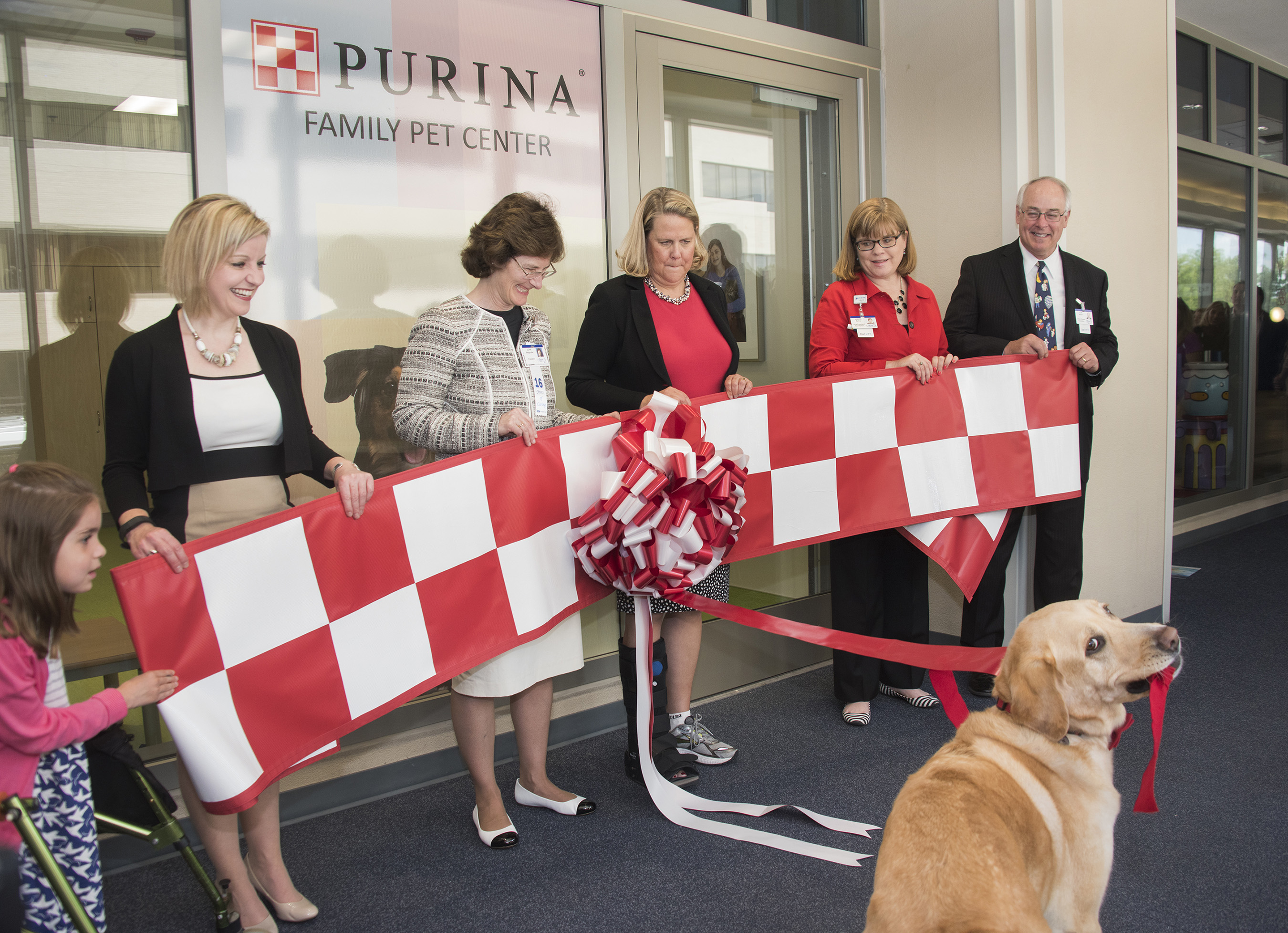 "The Purina Family Pet Center ""ribbon tugging"" ceremony was led by Golden Retriever-Labrador mix named ""Happy Jack."""