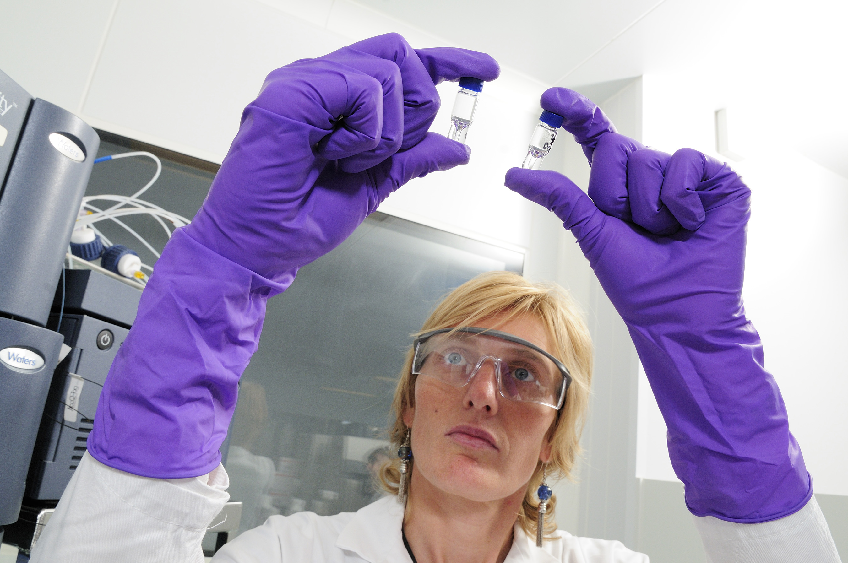 Scientist carefully inspects vials during the production process