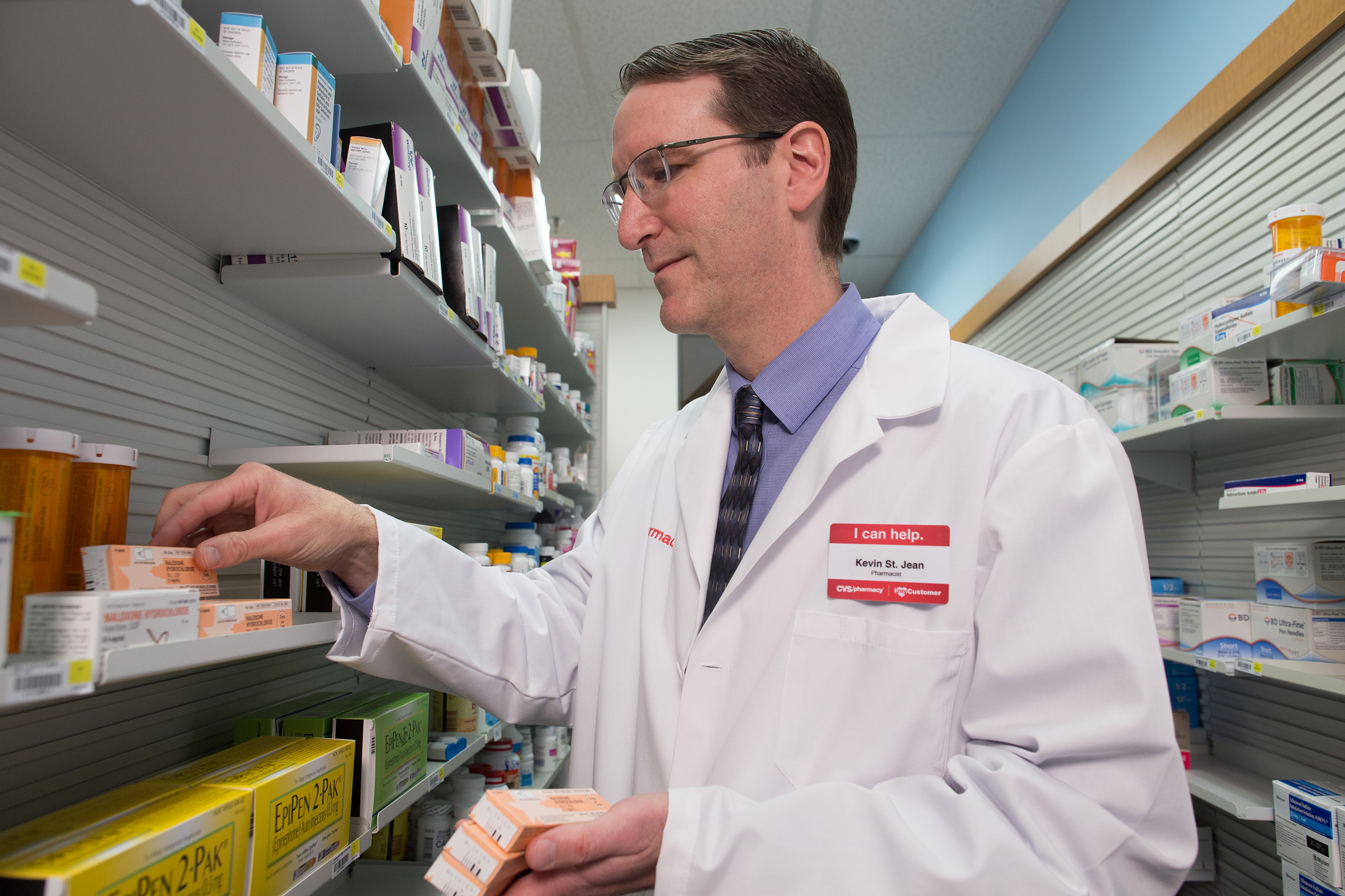 A CVS Pharmacist stocks the opoid-overdose reversal drug naloxone