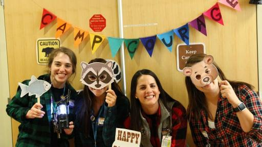 Four girls holding animal masks and signs