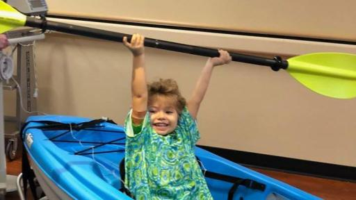 Child wearing a hospital gown, playing in a kayak inside a hospital room