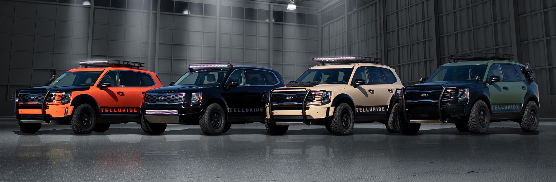 A row of 4 Kia Telluride SUV's in different colors inside a building.