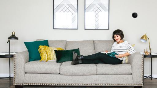 Woman lounging on grey couch, ecobee thermostat on the wall nearby