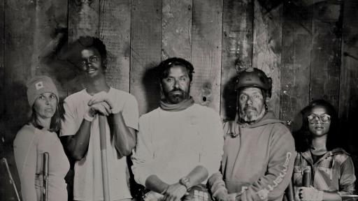 A group picture showing 4 people 2 men and 2 women with gardening tools.