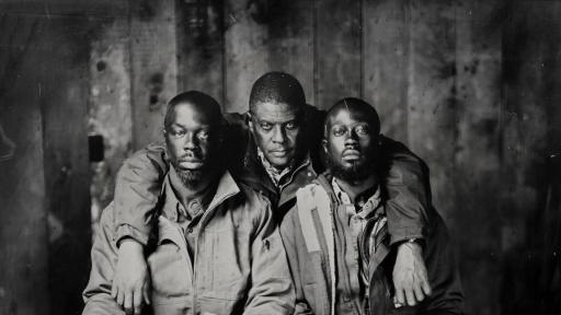 Three men in Carhartt work clothes posing for a photo.