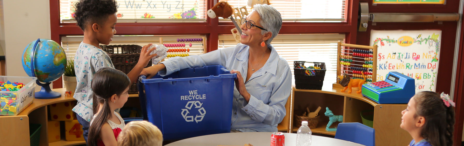 Woman holding recycling bin for children to toss recyclables into.