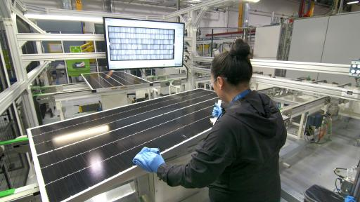 A woman testing solar cells in a factory.