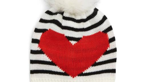 White beanie with black stripes and a furry pom at the top.