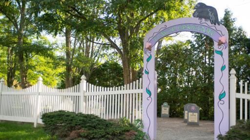 Ben & Jerry's Flavor Graveyard Entrance with white picket fence and headstones in inside.