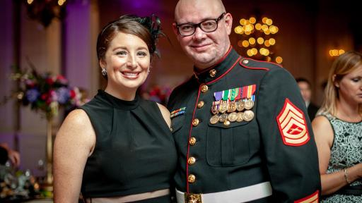 A highly decorated military member in full uniform standing with his wife for a photo.