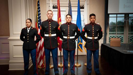 Four National Guard service members standing in front of flags in full uniform.