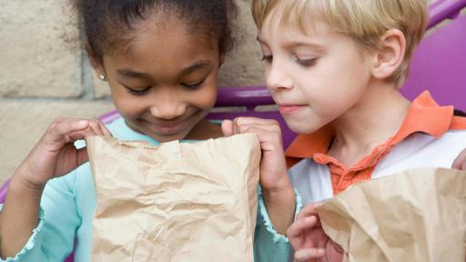 Girl and boy look into a brown paper bagged lunch