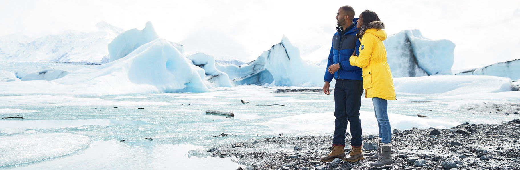 Couple outfitted with Lands End outwear, standing outside and enjoying an arctic view