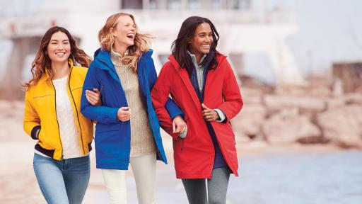 Three woman walking along the beach. Left wearing a yellow coat, middle in and blue coat, and right in a red coat.